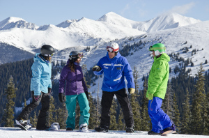 Adult snowboard instructor with students